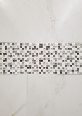 This porcelain has a subtle marble design. It looks great with a white and gray glass and marble mosaic.