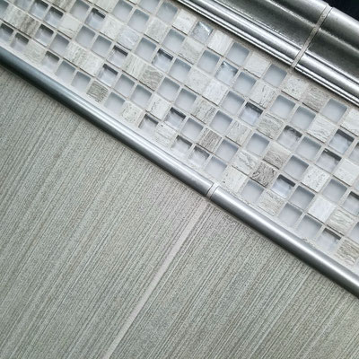 This taupe tile, grey glass and stone mosaic blend, and pewter trim have brown and lavender undertones.