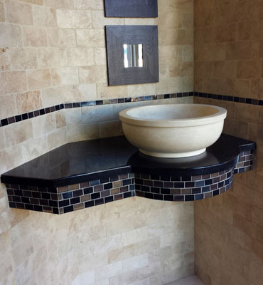 This ivory travertine sink perfectly matches the tumbled travertine wall and contrasts nicely with the Black Galaxy granite and bronze and black glass mosaic.