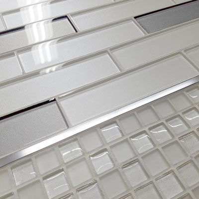 Shimmery white and gray glass backsplash with chrome trim