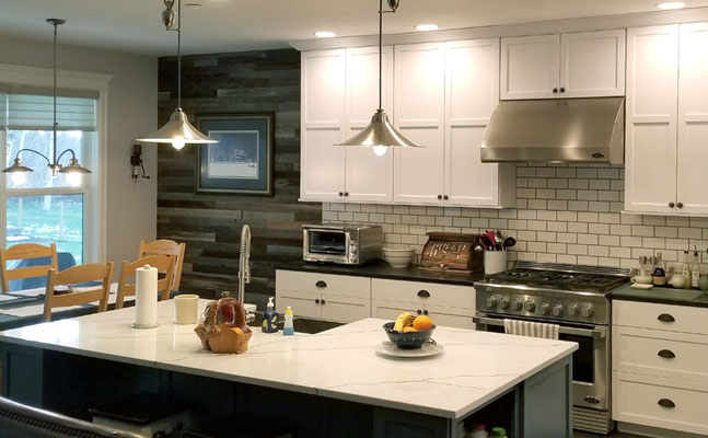 Firey Family Construction worked on the backsplash, floor tile, and wood feature wall in this stellar kitchen!
