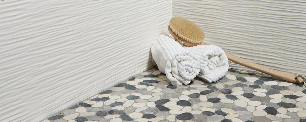 Pairing these pebbles with a modern 3D wall tile creates a sophisticated feel.