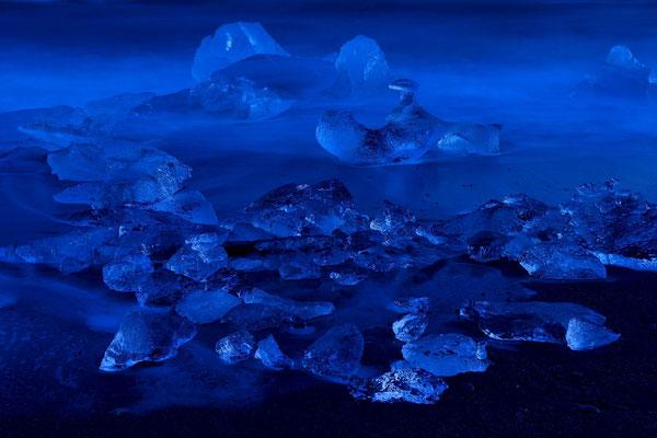 Eisbrocken des Breidamerkurjökull, angeschwemmt an den schwarzen Lavasandstrand der Küste vor Jökulsarlon; hier zur blauen Stunde