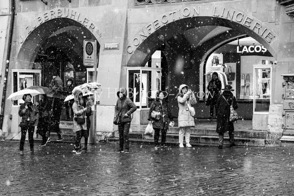 Asiatische Turisten warten im Schneegestöber auf das Glockenspiel am Zytglogge, Bern
