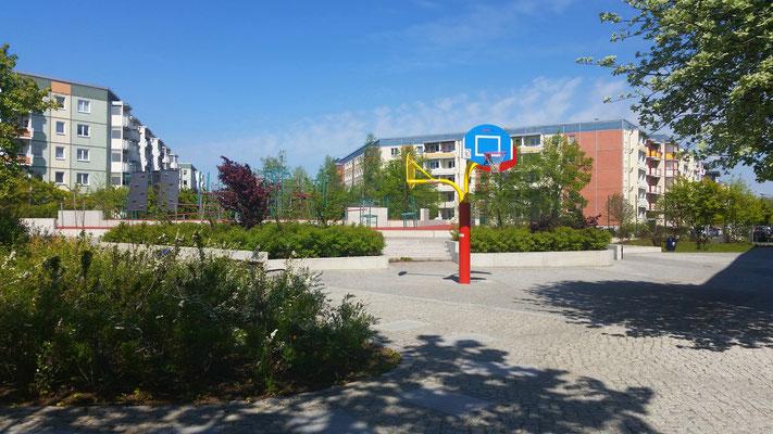 Der Spiel- und Bewegungshof nördlich von Haus 1; links die Albert-Kuntz-, rechts die Adele-Sandrock-Straße