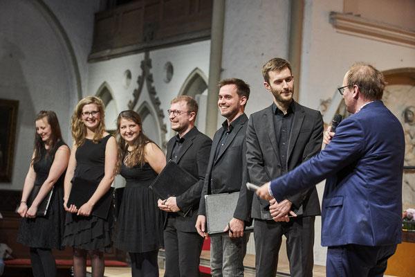 Vocoder Ensemble - Konzert in Hauptkirche St. Petri in Hamburg. Der Moderator stellt Fragen. Alle lachen.