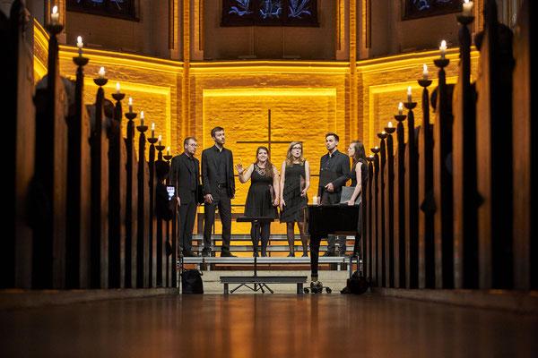 Vocoder Ensemble - stimmungsvolles goldenes Licht ist in der Hauptkirche St. Petri. Foto durch den Gang der Kirche der mit Kerzen bestückt ist.