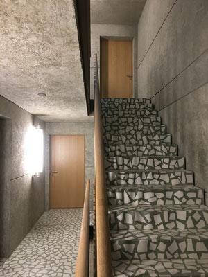 Treppenhaus mit Terrazzo, Sichtbeton, Handlauf und Wohnungstüren aus Eichenholz