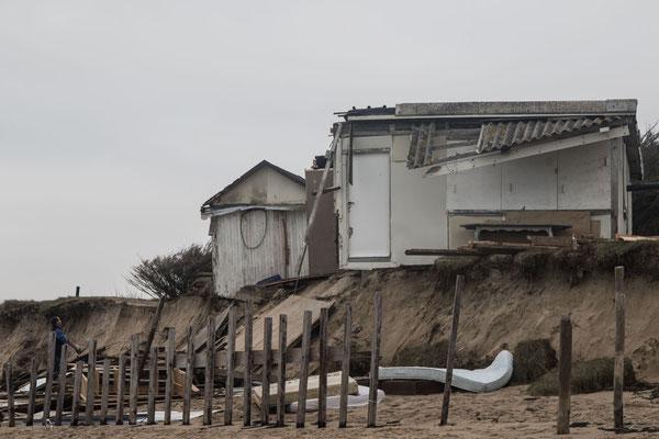 Wohl nicht mehr zu retten ist diese Hütte auf der Düne, ein Mann sortiert die Trümmer (Blainville-sur-Mer, 8.1.2018)