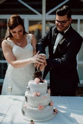 Das Brautpaar schneidet die dreistöckige Hochzeitstorte an