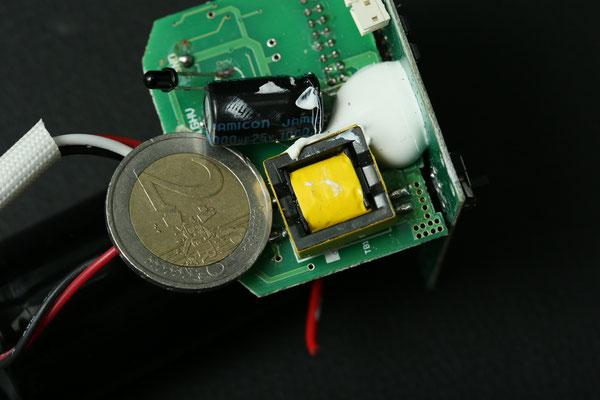 Das kleine, viereckige gelbe Kästchen - ist der Hochspannungstransformator eines Speedlights (Geldstück für Größenvergleich), er muss enormen Leistungen auf kleinstem Bauraum standhalten. Eine hohe Betriebstemperatur ist die Folge.