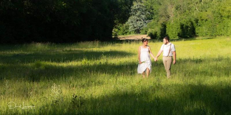 photo grossesse; couple thème champêtre nature promenade dans un champs