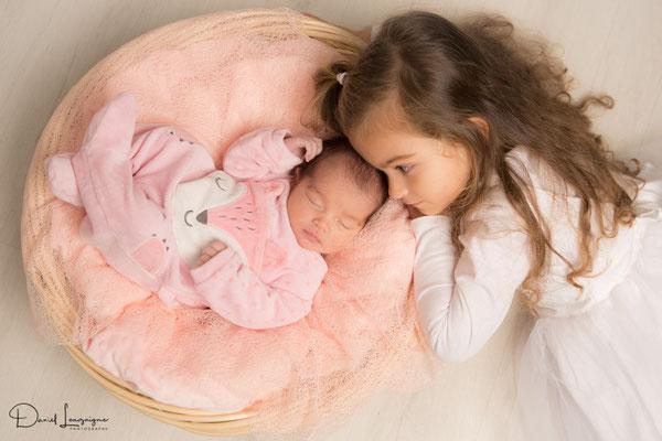 Shooting photo nouveau-né dans un panier avec grande sœur , studio Danimages dans le sud de l'Oise au portes du Val d'Oise