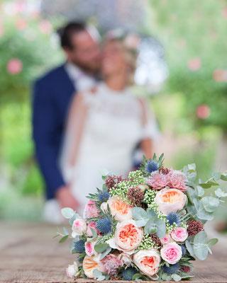 photo de couple de mariés ; derrière le bouquet de fleurs