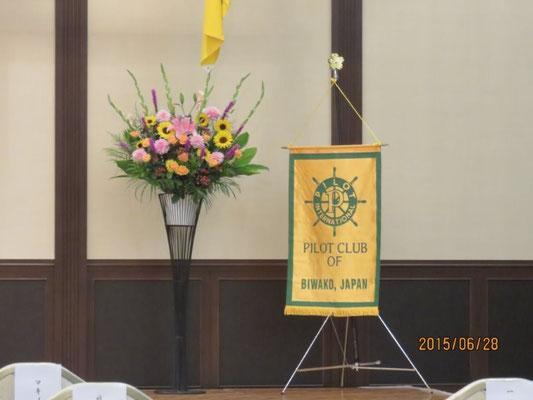舞台上に飾られた花とクラブ旗