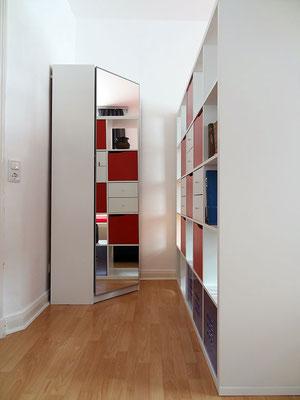 Der Kleiderschrank und der Raumteiler bieten Stauraum für Kleidung o.ä.