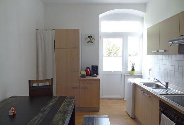 Wohnküche mit Zugang zum Balkon.