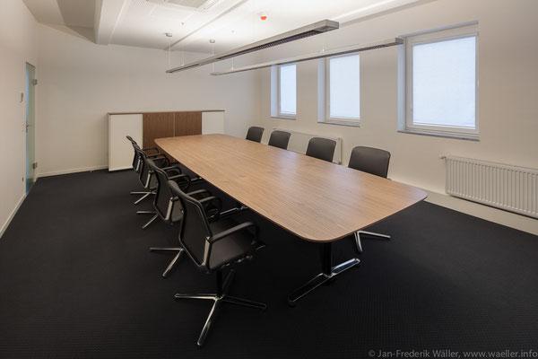 Konferenzraum mit einem edlen Holztisch, rückdrehende Lederstühle hoher Qualität, hochwertiger Textilbodenbelag; Foto: Jan-Frederik Wäller