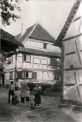 Am Waldprechtsbach Ecke Friedhofstrasse im Hinterhof. Das vordere rechte Haus ist das Haus Zimmer (Bild 17). Der hintere größere Mann ist Caspar Zimmer, der Besitzer des rechten Hauses.  Links sieht man einen kleinen Teil der Ölmühle Kühn.