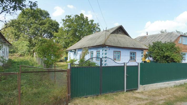 Wieder liebevoll gestrichene Häusschen mit farbigen Zäunen in der Westukraine