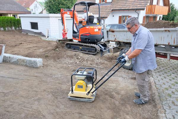 Der Boden wird verfestigt. Daneben wird mit grossen Gerät gearbeitet.