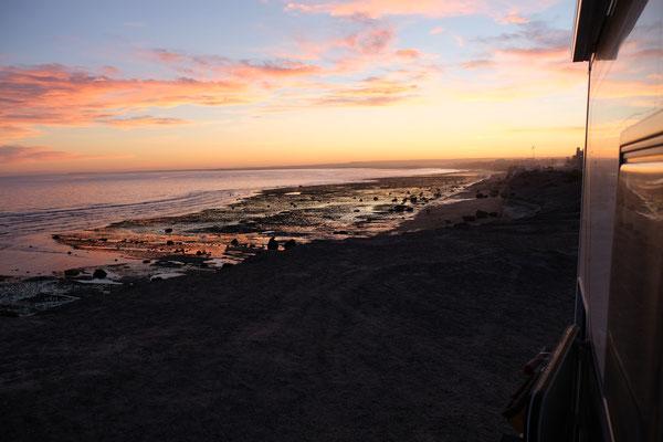 Die Sonne geht und die Badenden verlassen langsam den Strand von Las Grutas