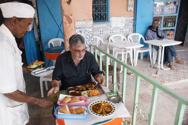 Der Koch serviert das feine Mittagessen.