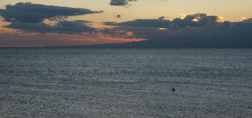 Wir stehen am Meer und schauen auf das umwölkte Sizilien auf der anderen Seite.
