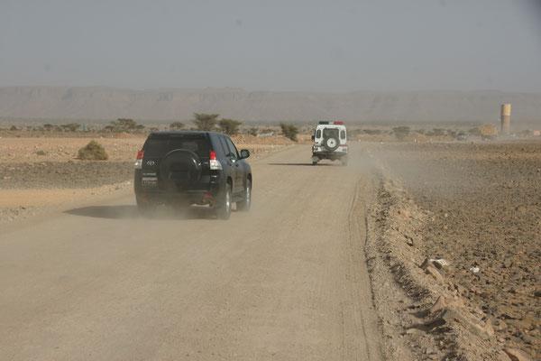 Zuvorderst die Polizei mit Blaulicht auf der Strecke nach M'hamid