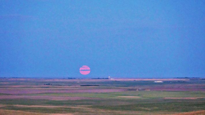 Am Horizont geht der rote Vollmond auf.