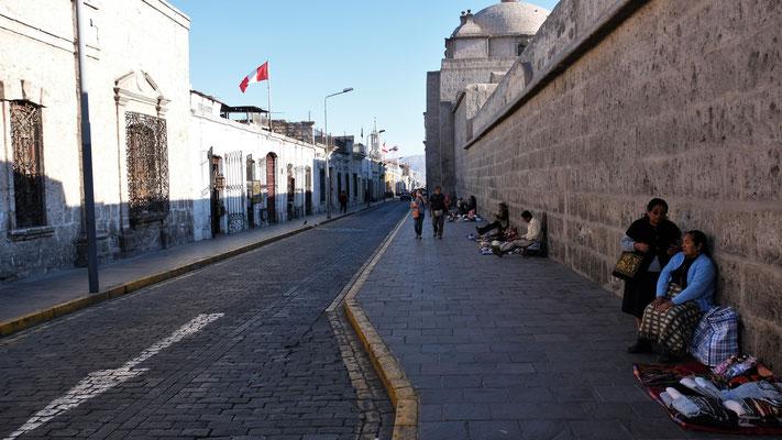 An dessen Mauern sich ebenfalls Händlerinnen postieren