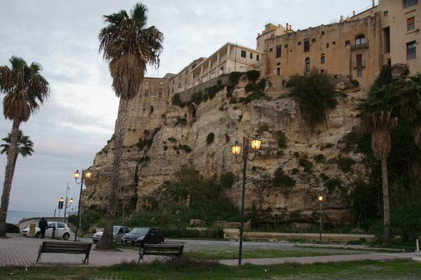 Blick von unten auf die Felsen und Mauern von Tropea und