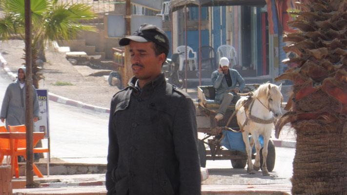 Man beachte: Der Mann auf dem Pferdefuhrwerk am Handy