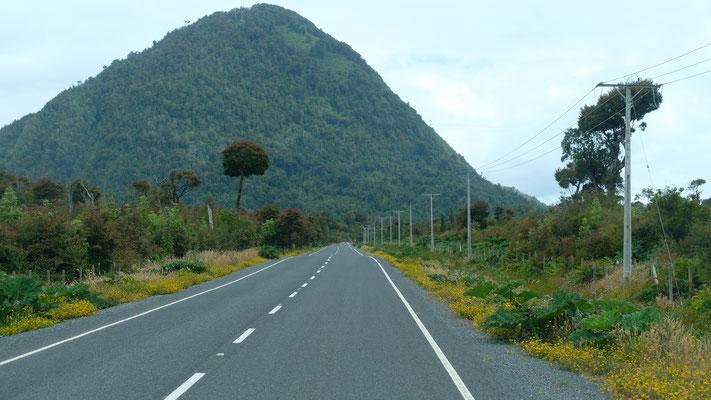 Auf der Strasse zum Flughafen, hinten einer der zahlreichen Vulkane