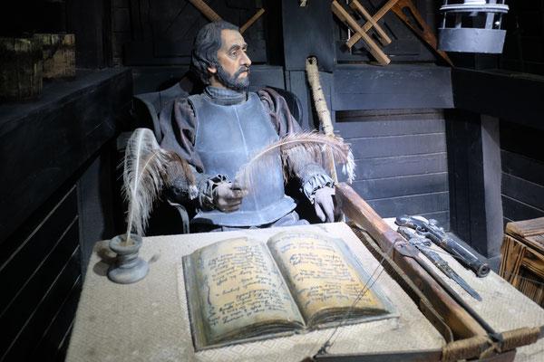Magellan hinter seinem Schreibtisch