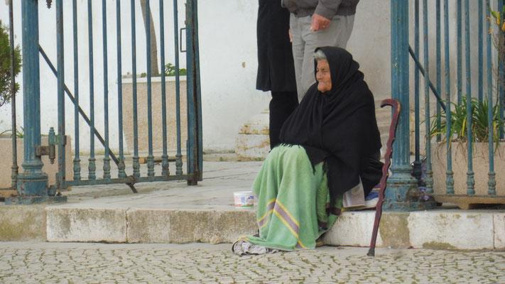 Wie im Mittelalter sitzt sie bettelnd vor der Kirche.