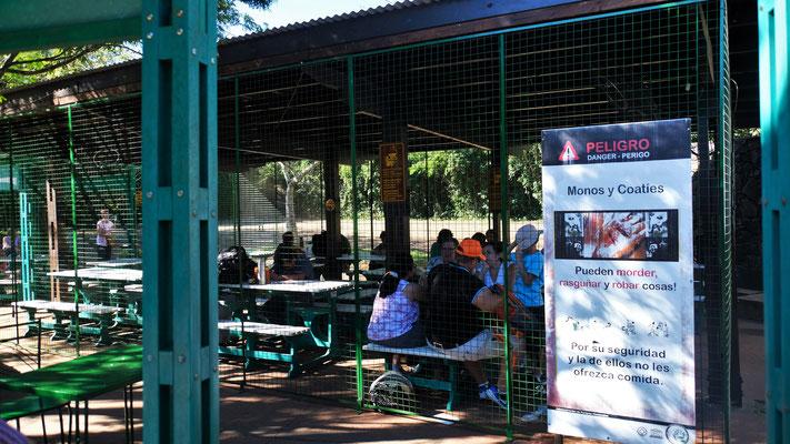 Einige Menschen bringen sich hinter diese Gitter zum ruhigen Essen in Sicherheit.