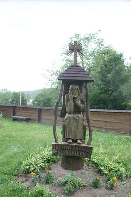 Holzfiguren vor der Kirche in Palüse