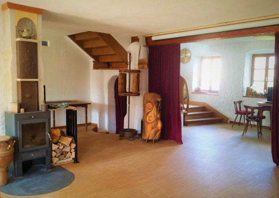 """""""getunter"""" Kaminofen, Treppe nach oben, Bühnenvorhang, Schlitztrommel und Denkmühlen (Gebetsmühlen aus Holunderholz)"""