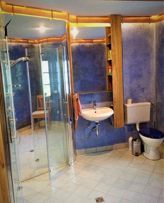 "Bathroom and toilet on the ground floor redesigned with tadelakt, ""upcycled"" aluminum mirror and bird's-eye maple veneer lighting strip"