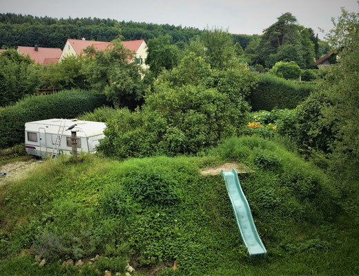 Wohnwagen- mit Rutschhügel und Gartenanlage