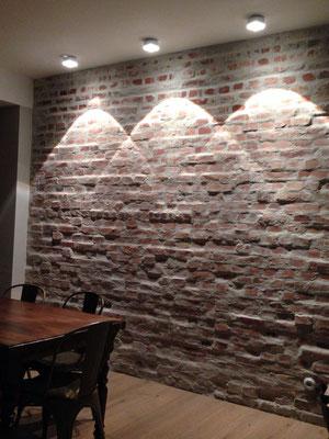 Deckeneinbauspots mit markanten Lichtkegeln setzten die Natursteinwand in Szene – Lichtplanung für ein  Einfamilienhaus in Köln