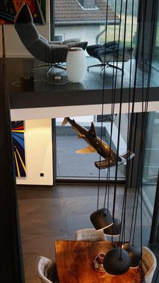 Blick vom Obergeschoss auf die skulptural abgehängte Pendelleuchte AIM von Flos