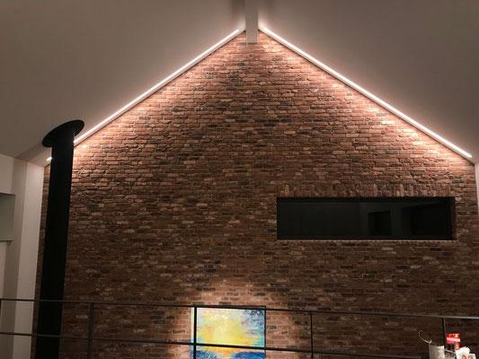 Deckenintegrierte Lichtlinien betonen die Materialität der Natursteinmauer
