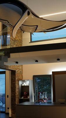 Eine deckenintegrierte Lichtlinie spendet zusammen mit einer Hinterleuchtung der Küchenmöbel Ambientelicht für Küche und Galerie
