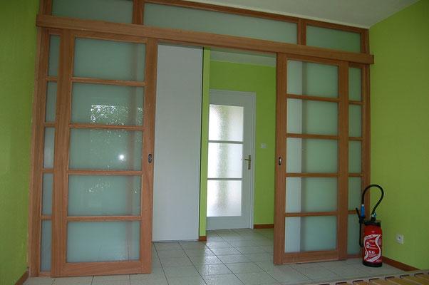 Portes coulissantes dans cloison et imposte vitrées, agrandissant l'espace en conservant la luminosité.