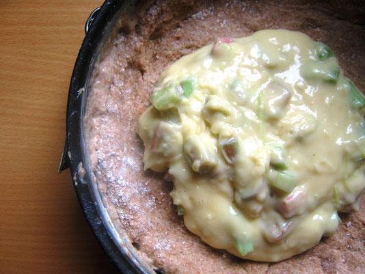 Den Pudding in die Springform geben und einige Rh.stücke draufstreuen