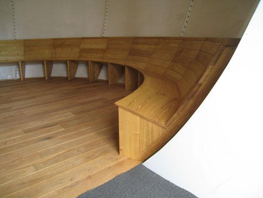 Runde Sitzbank für 25 Personen. Der Raum ist kugelförmig...