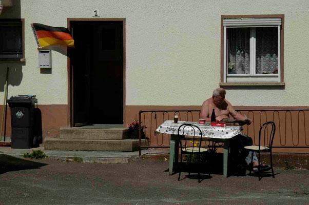 56- Deutschlandfahne vor deutschem Haus mit deutschem Zeitungsleser