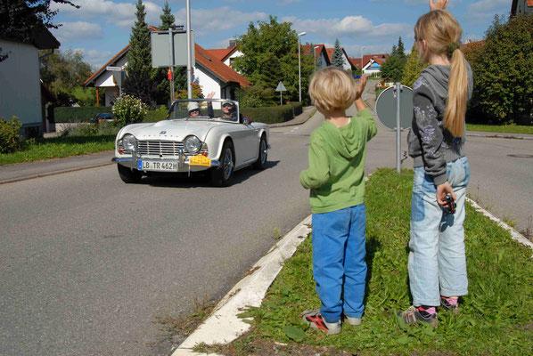 75 - Zwei Kinder winken Oldtimern bei einer Rallye